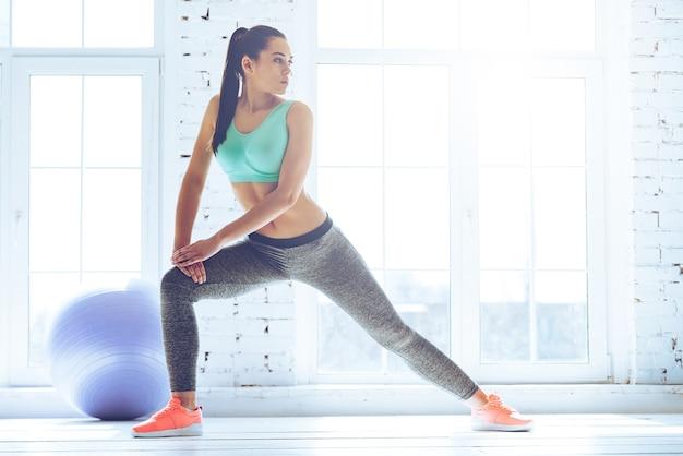 Rekken na een geweldige training. jonge mooie jonge vrouw in sportkleding die zich uitstrekt terwijl ze voor het raam in de sportschool staat