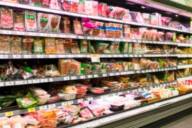 Rekken van verschillende fabrikanten van vleesproducten in pakketten in de winkel