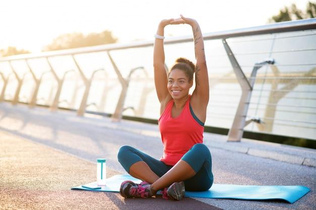 Rekken voor yoga. het glimlachen het donkere vrouw uitrekken zich vóór yoga terwijl buiten opleiding
