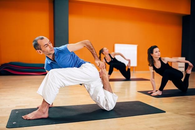 Rekoefening, vrouwelijke yogagroep in actie, training met instructeur, trainen in de sportschool. yogi binnen