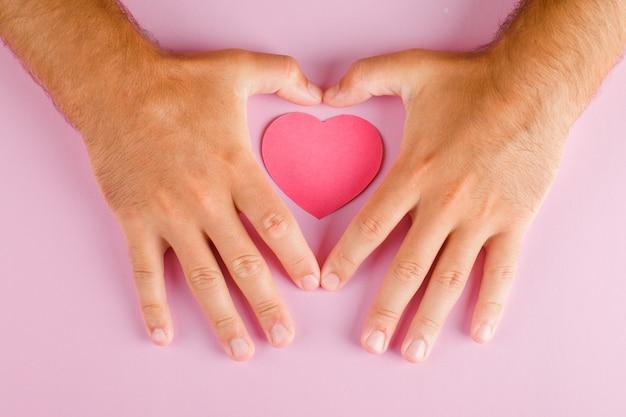 Relatie concept op roze tafel plat lag. handen beschermen papier gesneden hart.