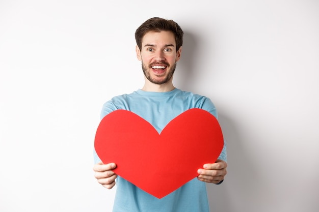 Relatie en mensen concept. knappe man geeft valentijnshart aan je, glimlachend en zegt ik hou van je op camera, staande op een witte achtergrond.