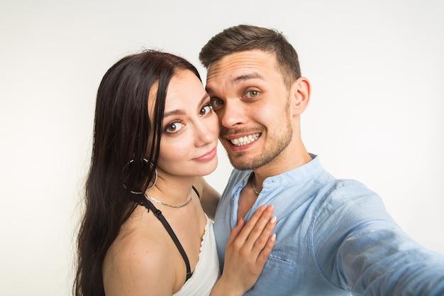 Relatie en mensen concept-man selfie te nemen met zijn prachtige vrouw op mobiele telefoon op witte achtergrond.