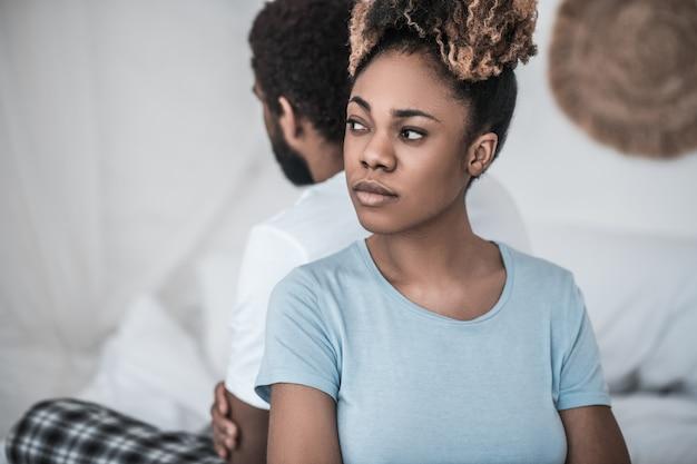 Relatie, probleem. droevige jonge afrikaanse amerikaanse vrouw in depressieve bui met terug naar haar echtgenoot die aan kant kijkt