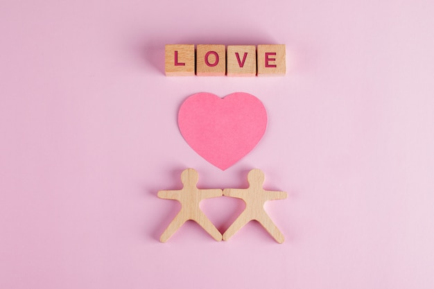 Relatieconcept met papier gesneden hart, houten kubussen, menselijke modellen op roze tafel plat leggen.