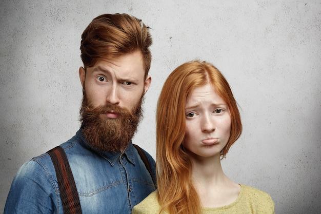 Relaties problemen concept. mooie roodharige jonge vrouw die haar lippen pruilt, boos en ongelukkig kijkt met haar vriendje.