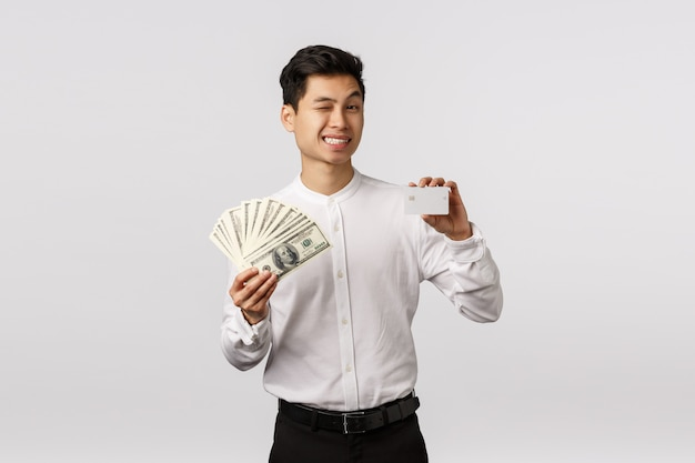 Relax bank heeft u gedekt. de brutale en ontspannen, vrolijke succesvolle aziatische zakenman knipoogt camera en het glimlachen, toont geld en creditcard, advies u contante storting zet, status