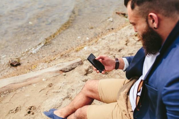 Relaxed man met zijn telefoon op het strand
