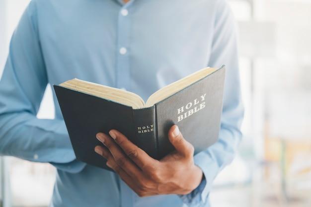 Religie christendom concept. man houdt en leest de heilige christelijke bijbel.