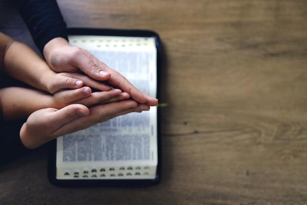 Religieus christelijk meisje dat met haar moeder binnenshuis bidt. bijbel op de achtergrond. ruimte voor tekst