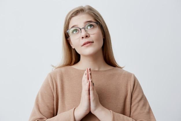Religieus meisje met blond haar in stijlvolle bril drukt handpalmen tegen elkaar en kijkt naar boven, bidt tot god, smeekt om vergeving of vraagt om haar droom te laten uitkomen. emoties en gevoelens