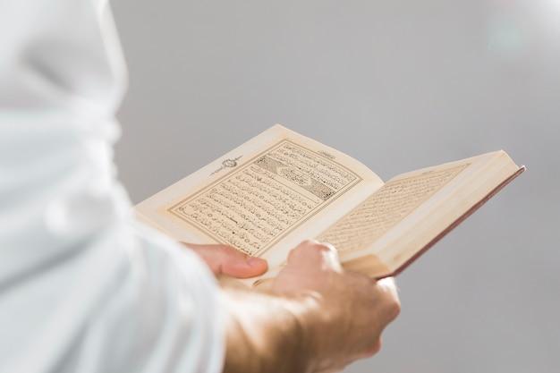 Religieus moslimboek dat in handen wordt gehouden