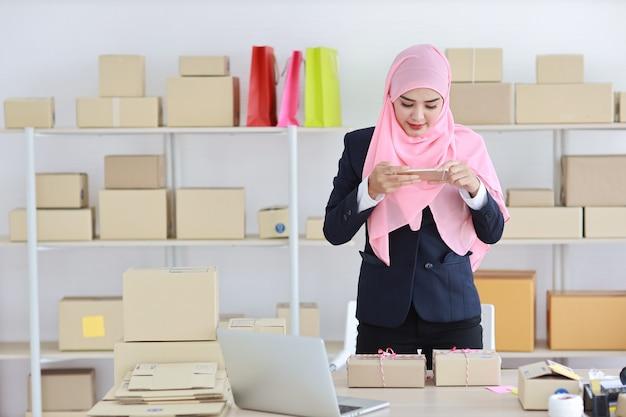 Religieuze aziatische moslimvrouw in blauw pak staat en neemt een foto van de pakketdoos die wordt afgeleverd vanaf de mobiele telefoon. start-up mkb freelance meisje werkt thuis met een blij lachend gezicht