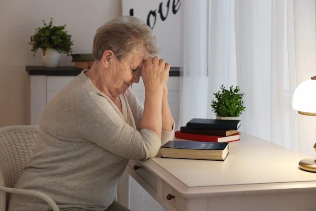 Religieuze bejaarde die over bijbel aan tafel bidt