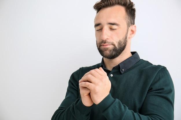 Religieuze jonge man bidden tot god op lichte ondergrond