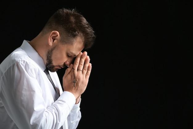 Religieuze man bidden op donker