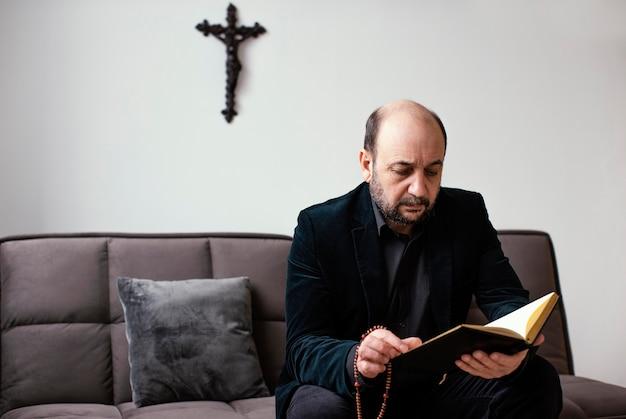 Religieuze man die thuis een heilig boek leest