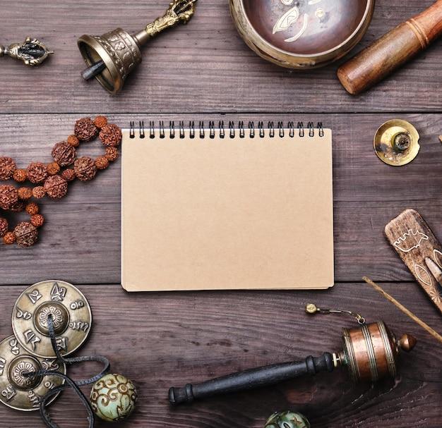 Religieuze muziekinstrumenten voor meditatie en alternatieve geneeskunde, leeg notitieboekje met bruine vellen