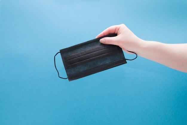 Remale hand olds zwart gezichtsmasker op blauwe achtergrond
