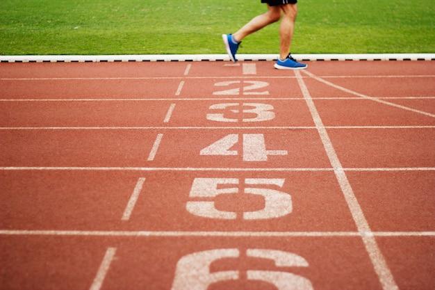 Renbaannummer en atletiekmensen die oefening op het spoorgebied openlucht in werking stellen