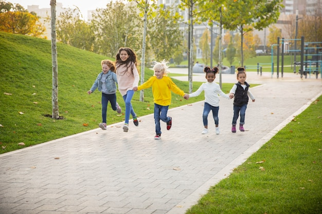 Rennen. interraciale groep kinderen, meisjes en jongens die samen spelen in het park in de zomerdag. vriendschap kent geen ras. geluk, jeugd, onderwijs, diversiteitsconcept. kijk blij en oprecht.