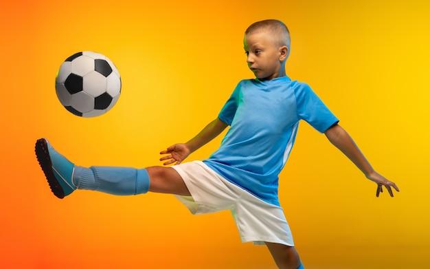 Rennen. jonge jongen als een voetbal of voetballer in sportwear die op gradiënt gele studio oefent