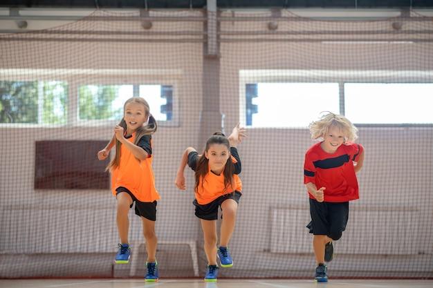 Rennen. kinderen in lichte sportkleding die in de sportschool lopen
