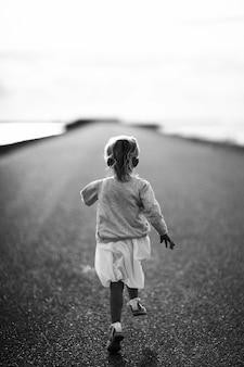 Rennend meisje, langs de weg in de vrouw traint door te rennen, joggen voor gezondheid, marathontraining,