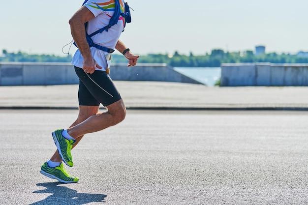 Rennende man. atletische man joggen in sportkleding op weg van de stad