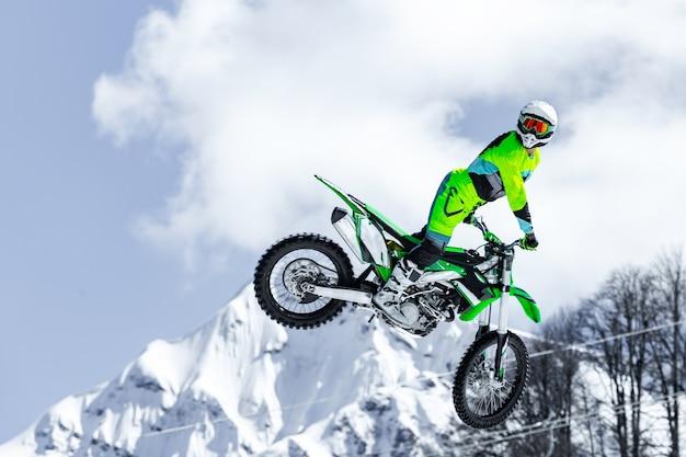 Renner op een motorfiets tijdens de vlucht, springt en stijgt op een springplank tegen de besneeuwde bergen
