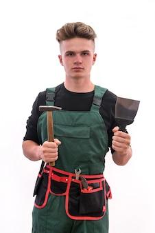 Renovatie concept. jonge man met tools geïsoleerd op een witte muur