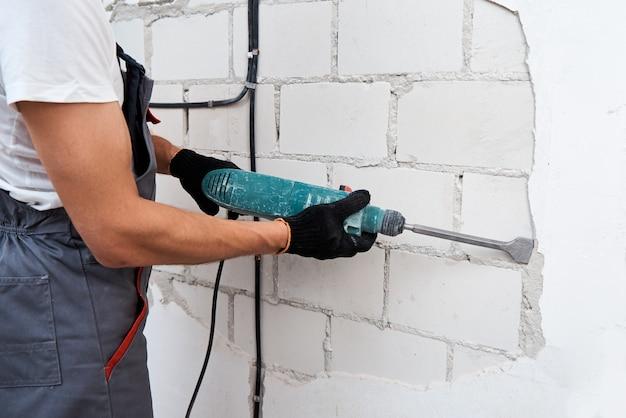 Renovatie concept. man met sloophamer verwijdert stucwerk van muur