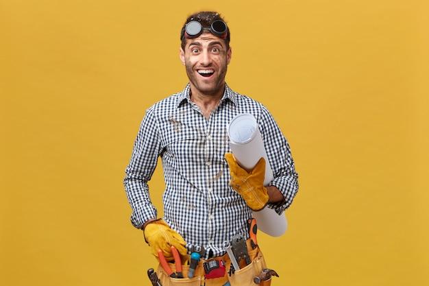 Renovatie- en bezettingsconcept. jonge klusjesman die een veiligheidsbril, een shirt en een kit vol met hulpmiddelen draagt die een blauwdruk vasthoudt en kijkt met opgewonden uitdrukking gaat rusten na het werk
