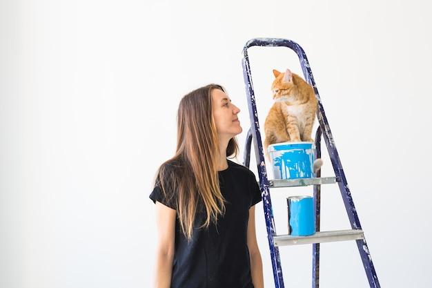 Renovatie herinrichting en familie concept jonge vrouw een kat aaien tijdens renovatie in appartement