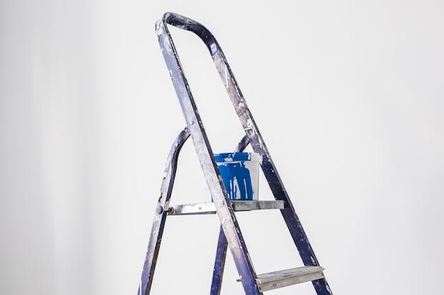 Renovatie-, herinrichting- en reparatieconcept. ladder met een container met blauwe verf over witte muur.