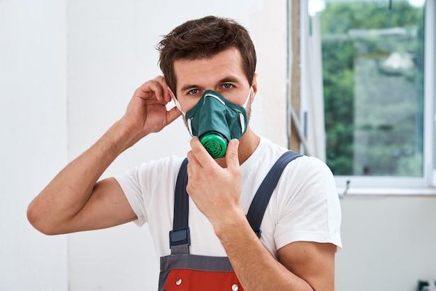 Renovatie klusjesman zet gasmasker op. portret van de werknemer van de huisreparatie