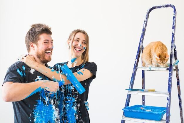 Renovatie reparatie en familie concept een jong stel met kat doet een reparatie in een nieuw huis