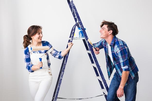 Renovatie, reparatie en mensenconcept. echtpaar gaat de muur schilderen en ziet er erg blij uit.