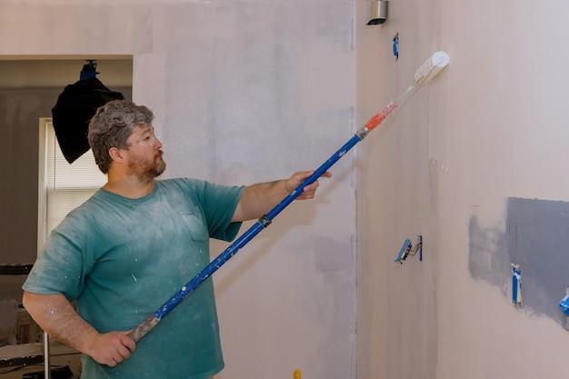 Renovatie van interieur, mannenhand schilderen muur met verfroller schilderen appartement, renoveren