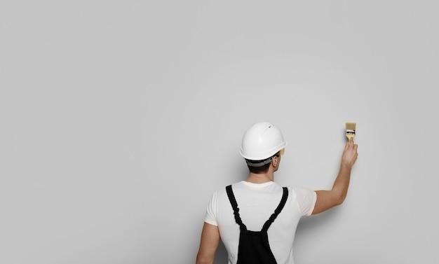 Renovatieconcept. close-up foto van de man in een werkpak en helm, die een muur in het wit schildert.