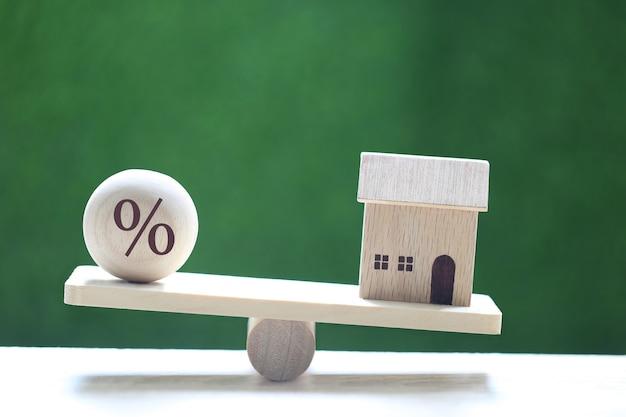 Rentetarief omhoog en bankconcept, modelhuis met drijvende rente op houten schaalwip op natuurlijke groene achtergrond, hypotheekrente