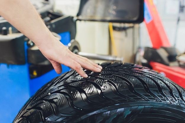 Reparateur balanceert het wiel en installeert de tubeless band van de auto op de balancer in de werkplaats.