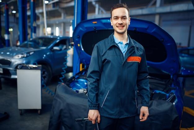 Reparateur bij voertuig met geopende motorkap, autoservice