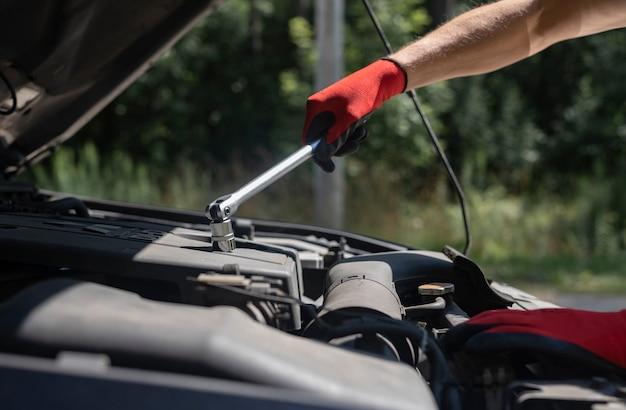 Reparateur die automotor repareert met moersleutel en open kap in de natuur