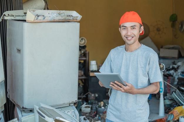 Reparateur glimlacht naar de camera terwijl hij zijn tablet-pc gebruikt rond kapotte elektronica in servicewinkel