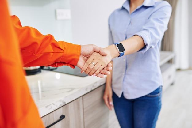 Reparateur hand schudden van huisvrouw na het beëindigen van het werk in de keuken