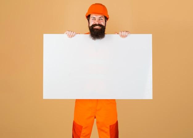 Reparateur in bouwvakker met reclamebanner. gelukkig bouwvakker in beschermende helm toont leeg bord.