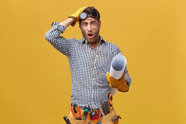 Reparateur in geruit overhemd, handschoenen, beschermende bril, opgerold papier vasthoudend met vies gezicht van het werk kijken met grote ogen en mond openen nadat iets verkeerd is gedaan
