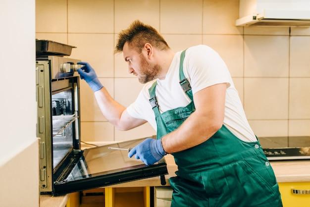 Reparateur in uniform controleert de oven, technicus
