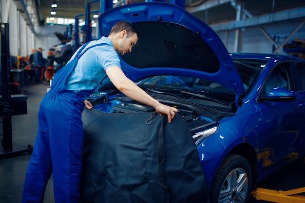 Reparateur in uniform controleert voertuigmotor, auto-servicestation. automobielcontrole en inspectie, professionele diagnostiek en reparatie